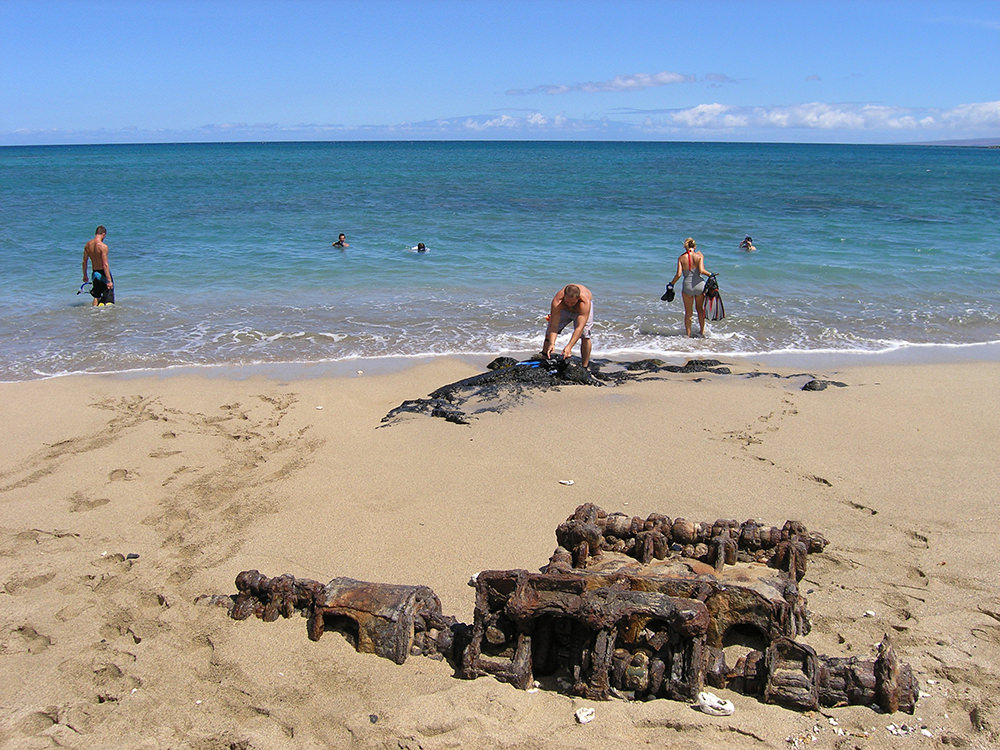 people on a beach near rusted engine parts