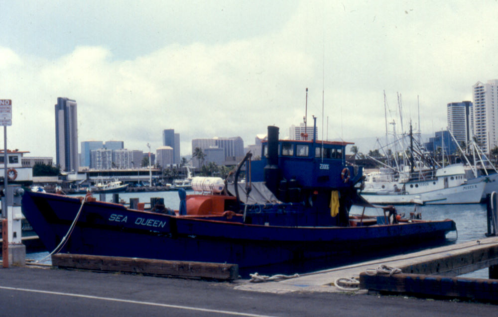 a blue ship with the name sea queen in harbor