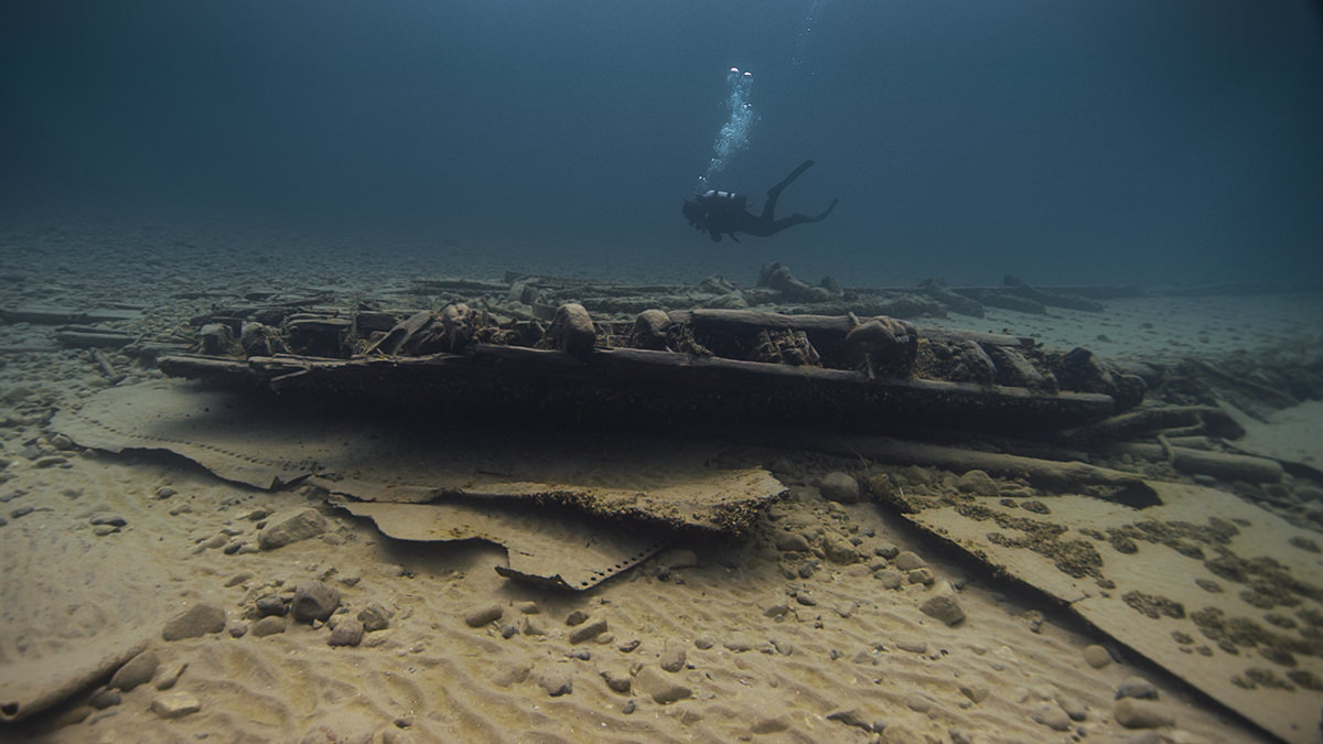 diver swimming by a shipwreck