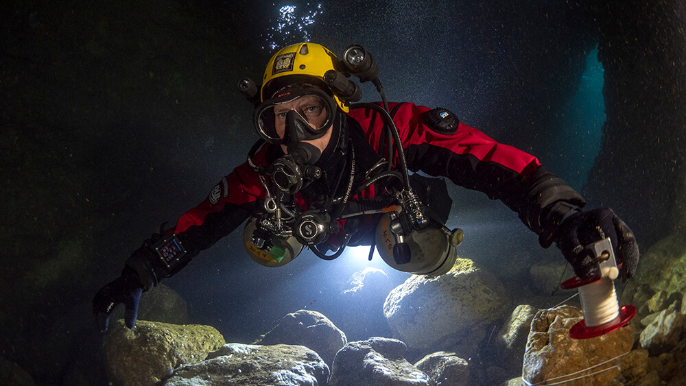 a diver swims through an underwater cave