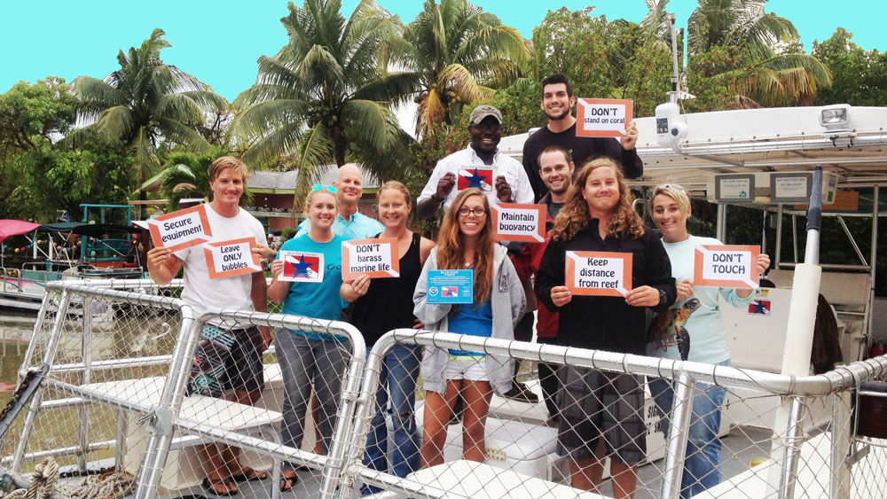 A group of people standing together on the back of a boat holding signs that read 'keep distance from reef' 'don't touch' 'leave only bubbles' 'secure equipment' 'dont stand on coral' 'don't harass marine life' 'maintain buoyancy'.