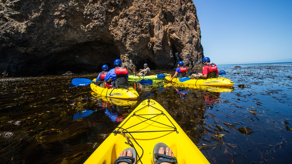 a group of kayaks approach a rock formation, from one kayak perspective