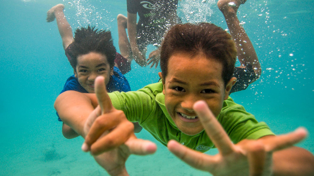 two kids smiling under the water towards the camera