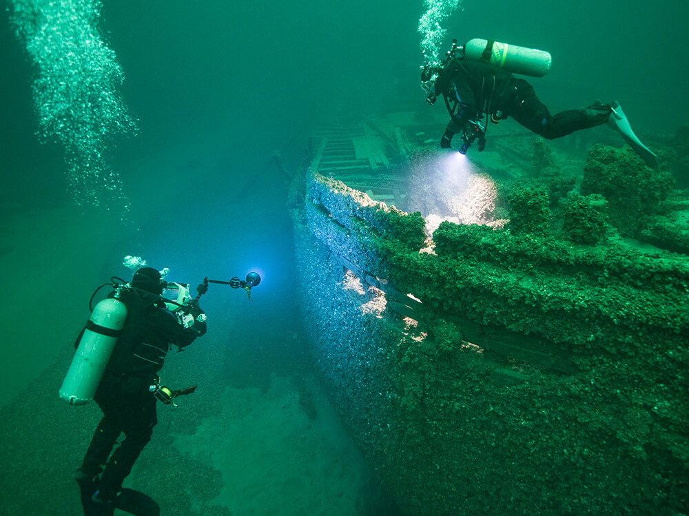 Divers shining their lights on a wooden shipwreck