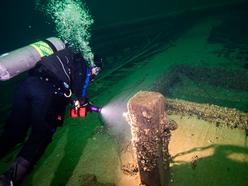 A diver swims along the deck of a wooden shipwreck