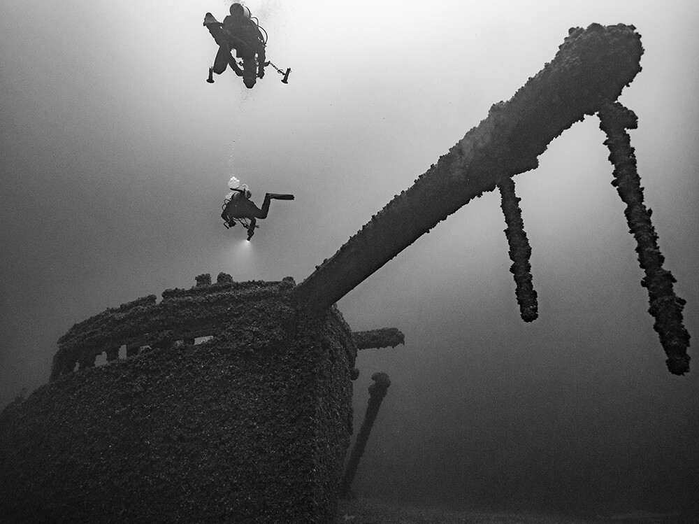 A black and white photo of two divers swimming above a shipwreck