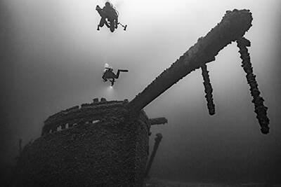 divers swim above the St. Peter ship wreck