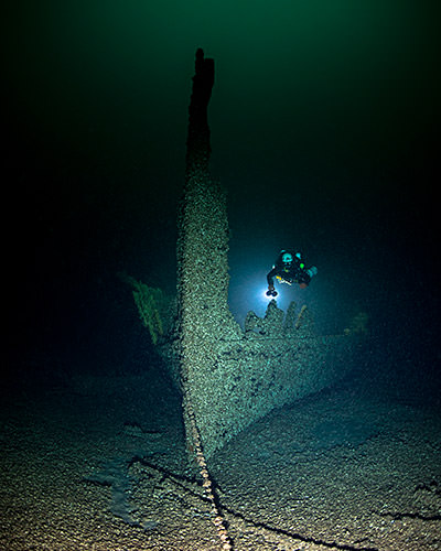 A diver inspects the bow of a shipwreck