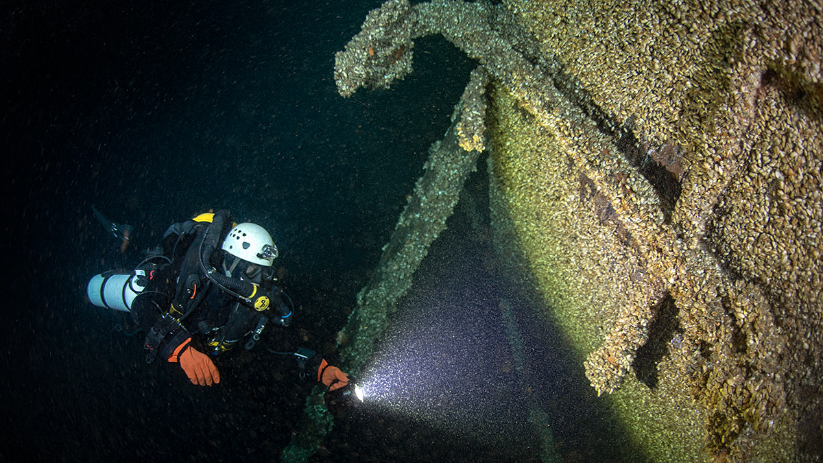 A diver inspects the bow of Queen of the Lakes, where the anchor remains in place