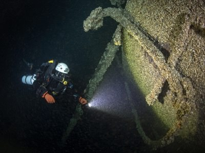 A diver inspects the bow of Queen of the Lakes