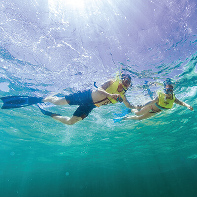 A man and women snorkeling and taking underwater photos