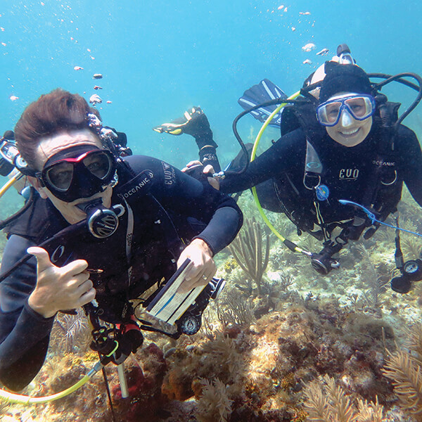 The diver on the left gives a thumbs up while the diver on right smiles