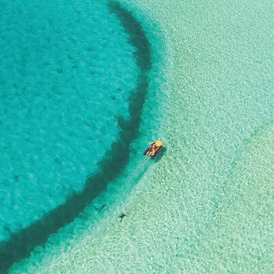 An aerial shot of a boat in crystal clear waters