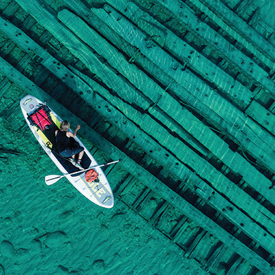 Aerial shot of a paddleboarder over a shipwreck in shallow water