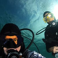 two divers take a selfie underwater