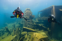 Two divers swimming next to the Nordmeet shipwreck