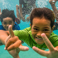 ChildreChildren swim in the tropical waters of National Marine Sanctuary of American Samoa
