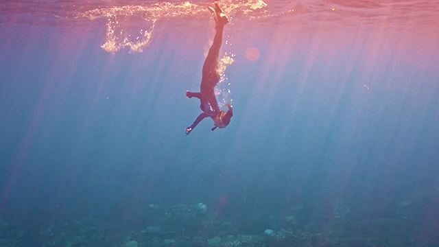 free diver breaking the surface of the water as she dives