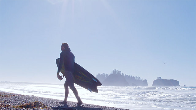 surfer with board in hand walking on the beach