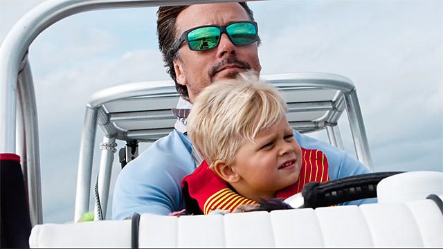 will benson with his son driving a boat