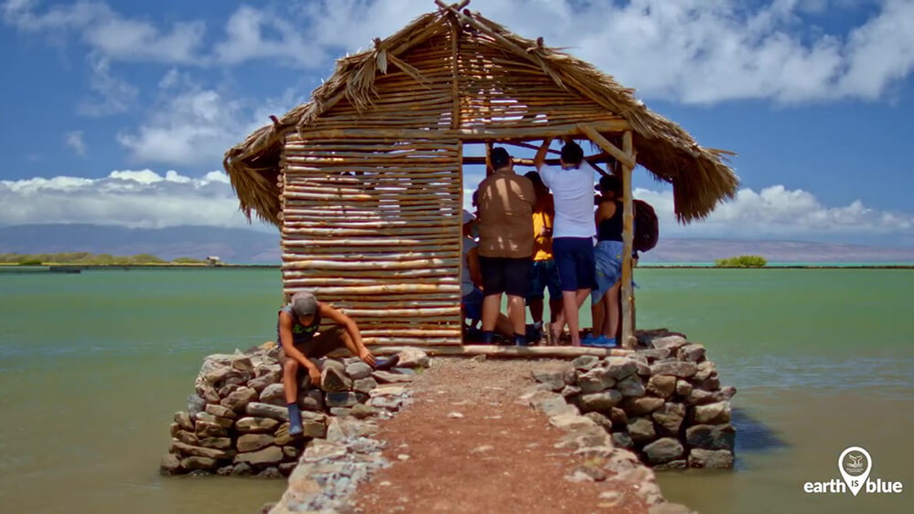 People work on a small hut near the ocean