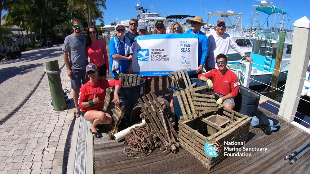 A group of people pose with marine debris they cleaned up